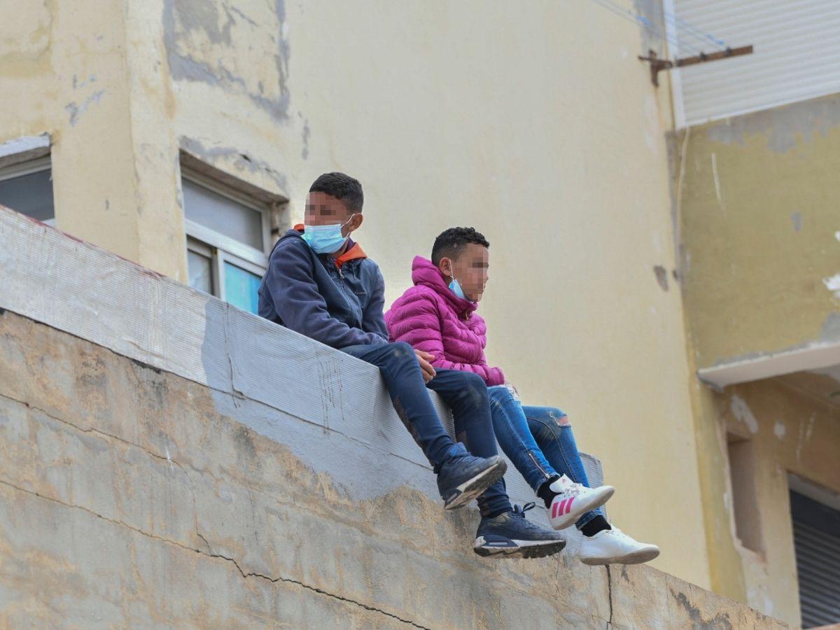 Dos niños sentados sobre un muro en la nave de primera acogida del polígono del Tarajal, a 20 de mayo de 2021, en Ceuta (España)